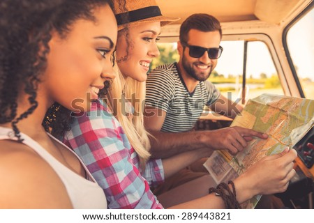 Planning their road trip. Side view of three cheerful young people examining map and smiling while sitting inside of their minivan - stock photo