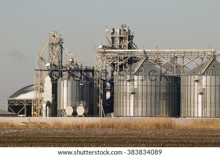 Plant for the drying and storage of grain. Rice plant in the middle of fields. - stock photo