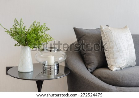 plant in white vase on round table with sofa and pillows in living room - stock photo