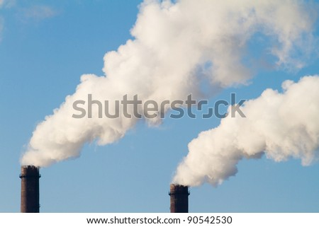plant pipe with smoke against blue sky - stock photo