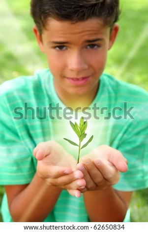plant sprout growing glow light on teenager boy hands outdoors [Photo Illustration] - stock photo
