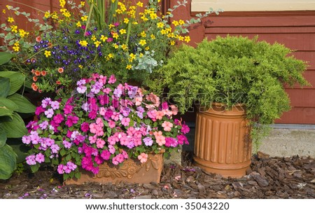 Planters used in the summer garden filled with impatiens, juniper, lobelia, petunia, marigolds and more. - stock photo
