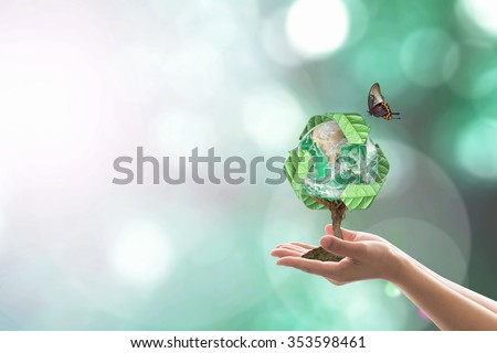 Planting eco friendly bio recycled arrow sign world tree on human hands w/ blur natural greenery:  Sustainable development CSR concept idea, saving environment: Elements of the image furnished by NASA - stock photo