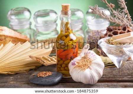 Plants for healthy lifestyle,garlic,  lemon grass, leaves, linseed and herbs in capsules with vegetables olives and pepper chilli in vinegar marinade. - stock photo