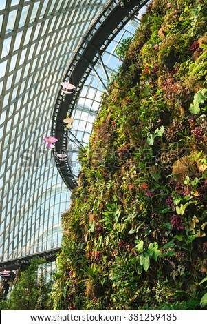 Plants growing from an artificial cliff face inside an enormous greenhouse, and an elevated catwalk for tourists and visitors. - stock photo