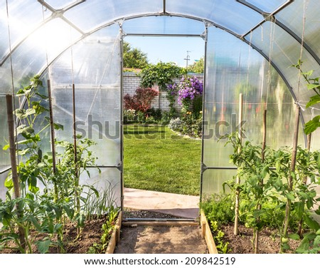 Plants growing in a translucent domed greenhouse or tunnel with a view from inside through the open door onto a pretty formal garden - stock photo