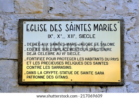plaque explaining the history of the church of Saintes-Maries-de-la-Mer. Dedicated to Saints Mary Jacobe and Salome and the Crypt containing the statue of Saint Sara patron saint of the Gypsies. - stock photo