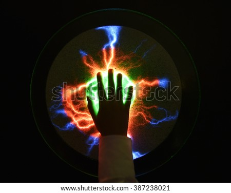 Plasma ball, if touched multicolor flashes appear  - stock photo