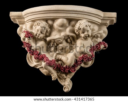 plaster decoration with angel and red roses on a black background - stock photo
