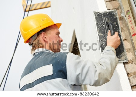 Plaster facade builder worker with roller at thermal insulation works - stock photo