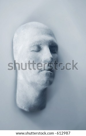 plaster face hanging on wall, abstract alone