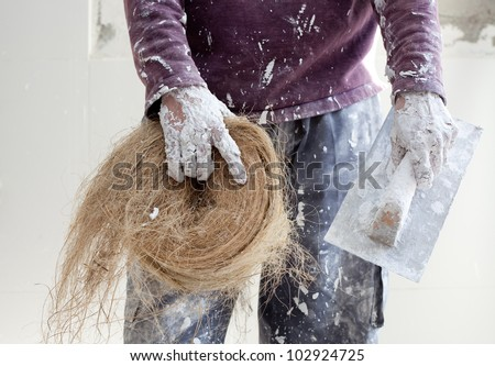 Plaster white dirty hand with hemp esparto for ceiling plasterboard construction - stock photo