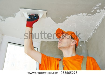 Plasterer at indoor ceiling renovation decoration with float and plaster - stock photo
