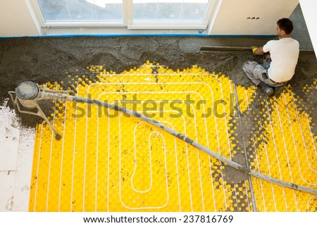 Plasterer at indoor concrete cement floor topping with float - stock photo