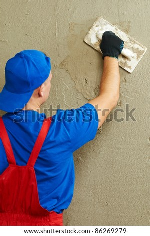 Plasterer at indoor wall renovation decoration with float - stock photo
