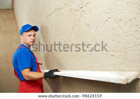 Plasterer at indoor wall renovation decoration with sleeker - stock photo