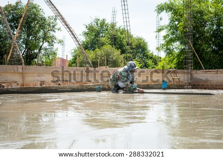 Plasterer concrete cement floor topping with float - stock photo