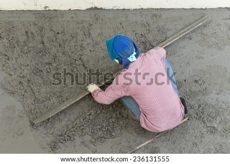 plasterer concrete cement worker plastering flooring of house construction - stock photo