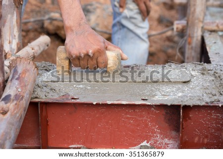 plasterer concrete worker at beam being constructed at construction site - stock photo