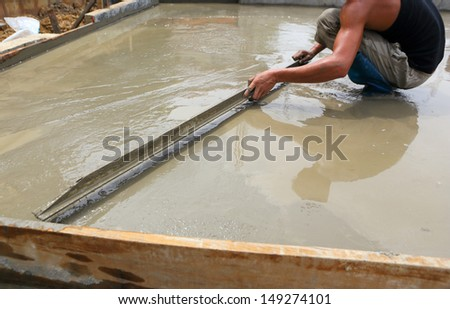 plasterer concrete worker at floor work - stock photo