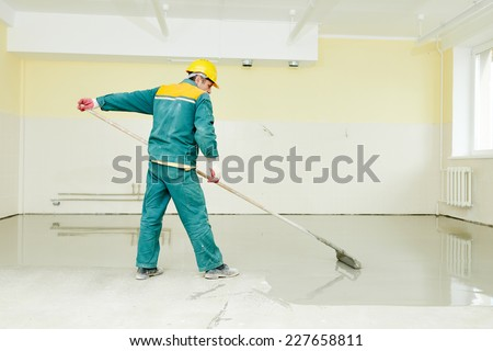 plasterer during floor covering works with self-levelling cement mortar - stock photo