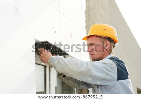 Plasterer facade builder worker with scratching tool at thermal insulation works - stock photo