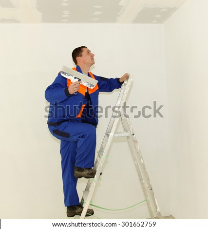 Plasterer with ladder in the room - stock photo
