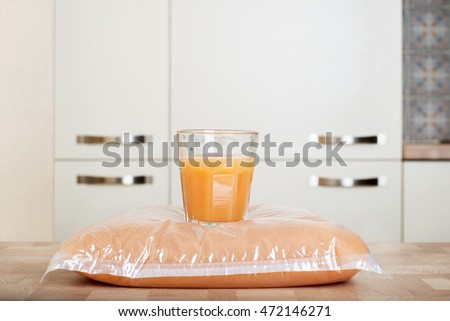 Plastic bag and glass full of apple juice on the wooden table