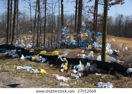 Plastic bags blown by wind from a landfill - stock photo