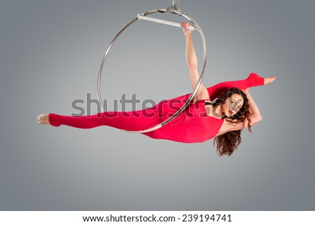 Plastic beautiful girl gymnast on acrobatic circus ring in flesh-colored suit. Aerial ring. - stock photo