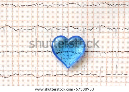 plastic blue heart on ECG (electrocardiogram) paper - stock photo