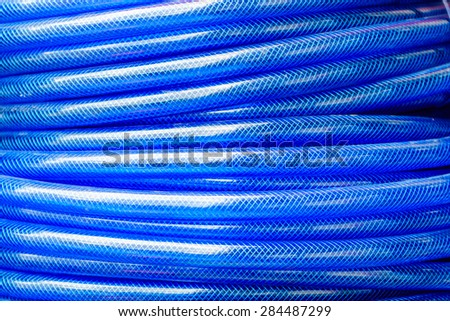plastic blue rolled up hose or cable  - stock photo