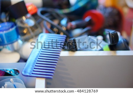 Plastic blue used comb on a messy drawer