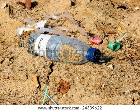 plastic bottle and trash on beach sand - stock photo