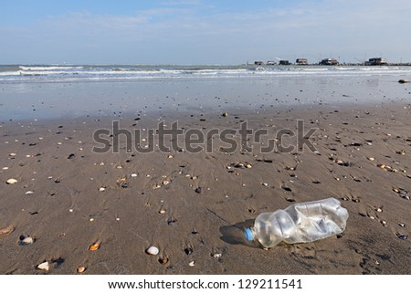 plastic bottle litter on the beach - landscape of seaside with fishing hut on background - stock photo