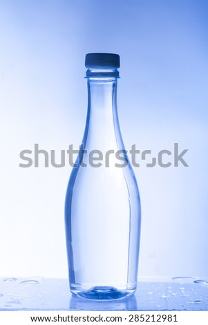 Plastic bottle of drinking water isolated on  blue background - stock photo
