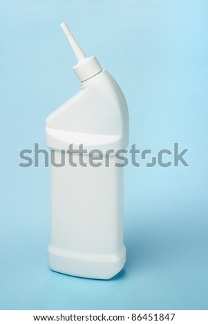Plastic bottle of toilet bowl cleaning product on blue background - stock photo
