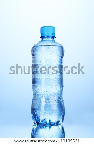plastic bottle of water on blue background - stock photo