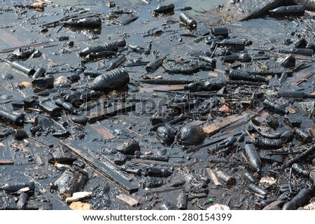 Plastic bottles and garbage floating on  fuel oil contaminated  ocean water - stock photo