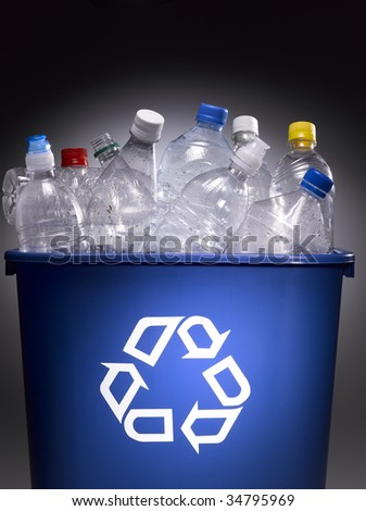 Plastic bottles in trash bin with recycle sign - stock photo