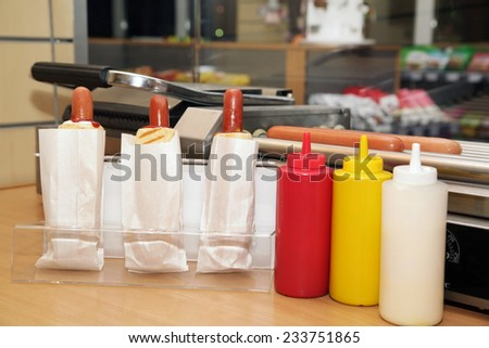 Plastic bottles with tasty sauces for of hot  hot dogs - stock photo