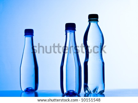 Plastic bottles with water against blue gradient background. Shallow DOF. - stock photo