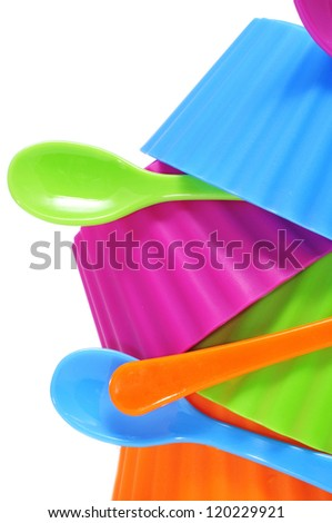 plastic bowls and spoons of different colors on a white background - stock photo