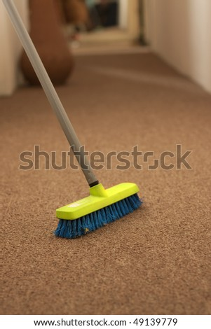 Plastic broom on carpet - stock photo