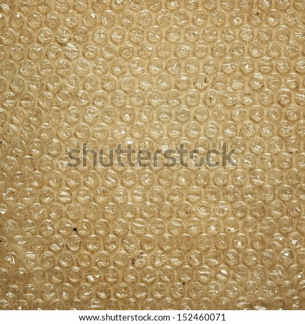 Plastic bubble packaging material on brown background - stock photo