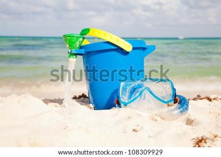 Plastic bucket and swim mask on the sand - stock photo