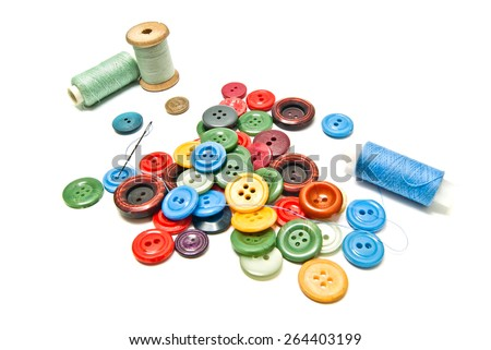 plastic buttons and spools of thread on white  - stock photo