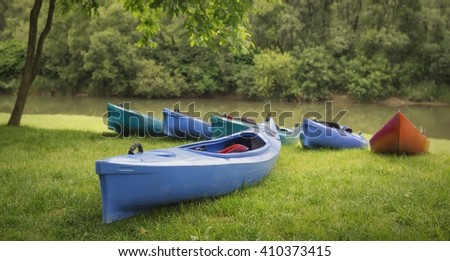 Plastic canoes on the river bank - stock photo