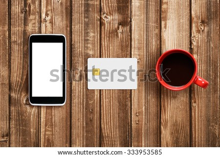 Plastic card, smartphone and coffee cup on wooden table - stock photo