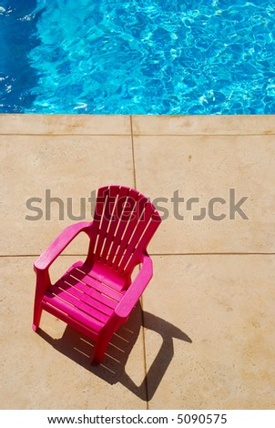 Plastic chair near vibrant blue swimming pool water - stock photo